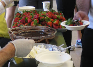 Tray of fresh strawberries, bowls of chocolate ganache and whipped cream.