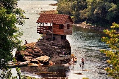 Cabaña sobre una roca gigante en un río hecha con madera reciclada.