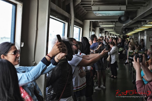 Tourists line the railings of a Staten Island Ferry and take selfies as it passes the Statue of Liberty. Travel photography by Kent Johnson.