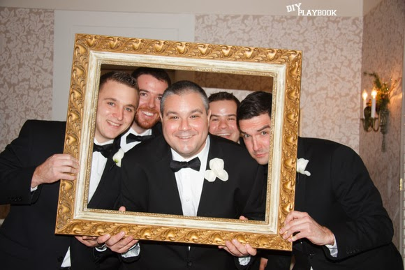 Groomsmen gather for a group photo behind a lovely vintage frame