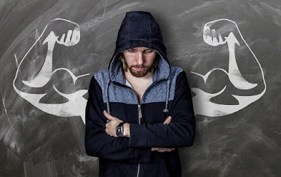 dude hunching in front of chalkboard with drawn-on biceps