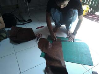 memotong bahan tas kulit