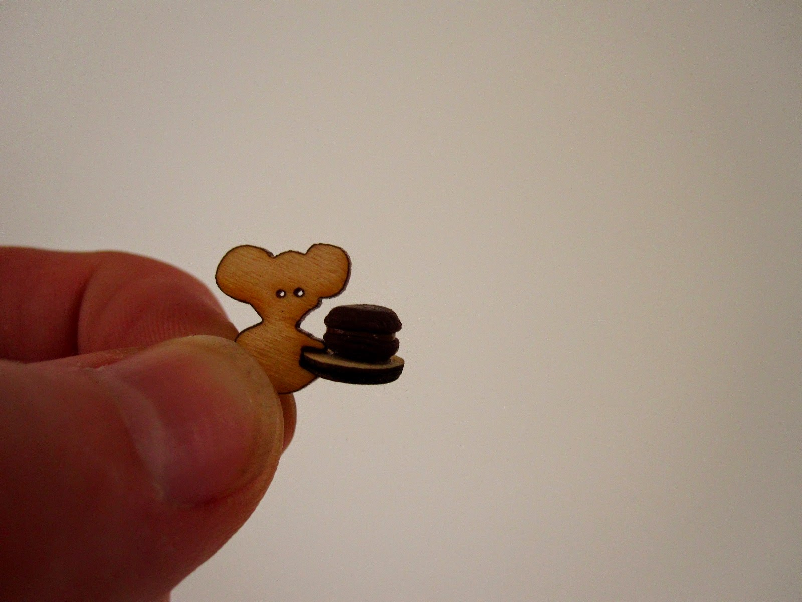 A tiny laser-cut wooden koala, holding a tray with a miniature macaron on it.
