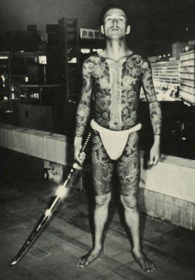 Miembro de la Yakuza armado con katana y tatuado con irezumi, en algún lugar del siglo XX