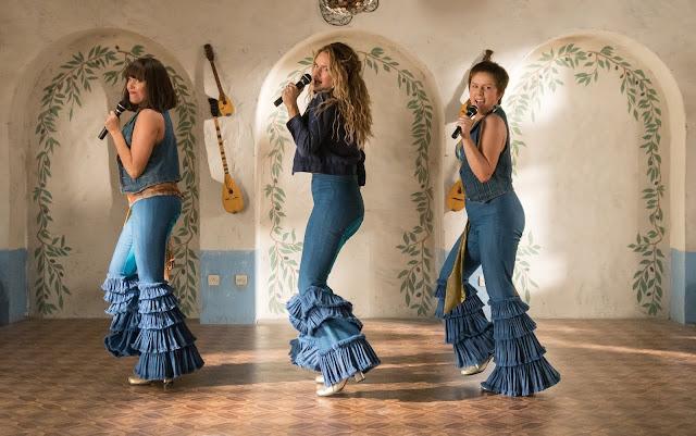Em Mamma Mia 2, Donna e suas amigas, Rosie e Tanya, cantam e dançam em cima de um palco.