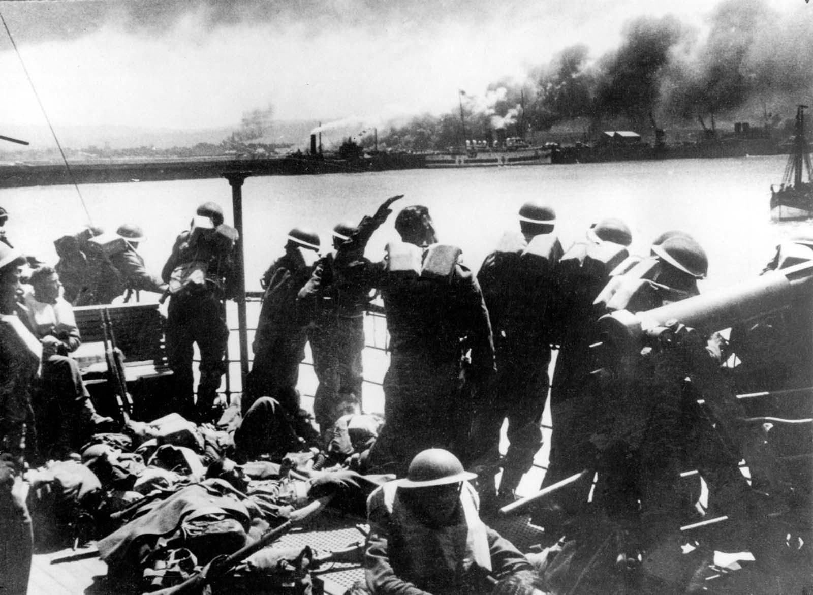 British Expeditionary Forces view the German bombardment of Dunkirk from an evacuation transport.