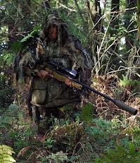 Üzerindeki yapraklı ve otlu kamuflaj ile ormanlık arazide kamufle olmuş bir keskin nişancı askeri