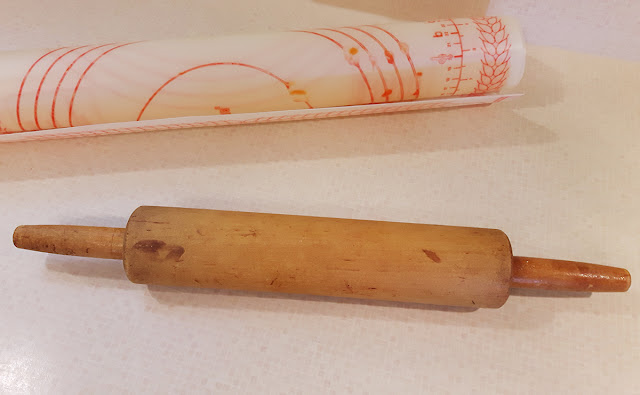 An older wooden rolling pin borrowed from a neighbour, with a rolling sheet.