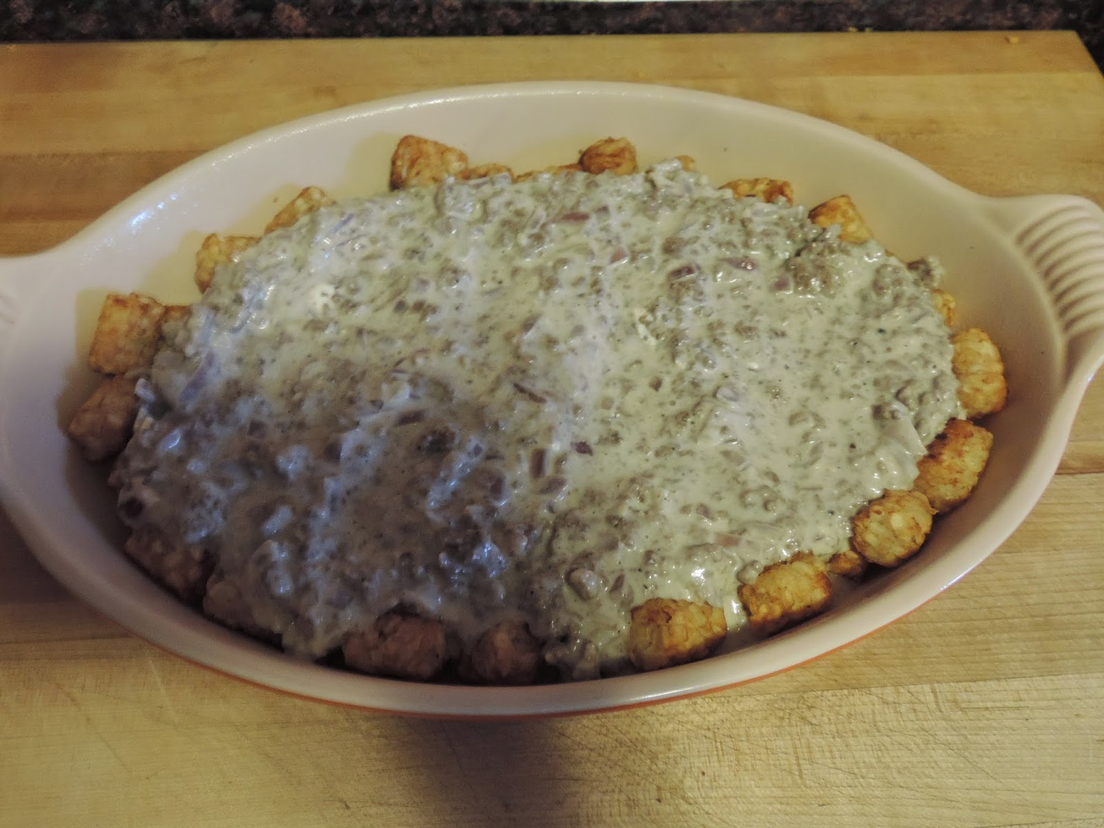 The stroganoff sauce poured over the tater tots.