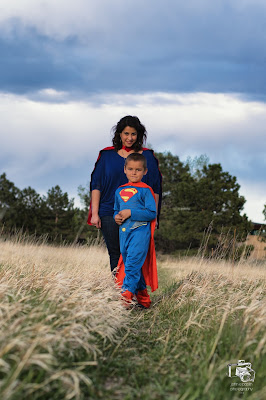 a boy in a superman costume poses for a photo in a field with his big sister