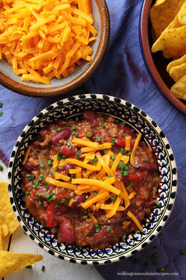 Chili with shredded cheddar cheese, nacho chips in bowls from Walking on Sunshine Recipes