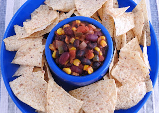 overhead shot of chips and dip in a blue serving platter