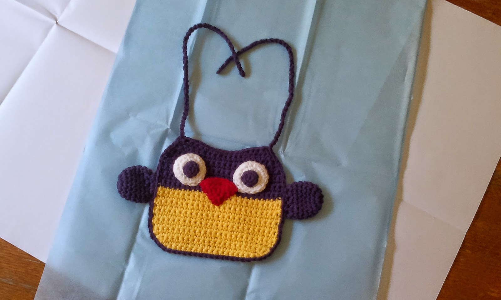 Crocheted owl bib laid out on two layers of wrapping paper. The ties and top half of the bib are purple: the bottom half is yellow. The bib has a purple border with purple wings on the sides. A red triangle is the beak and the eyes are made up of a small purple circle laid over a larger white circle.