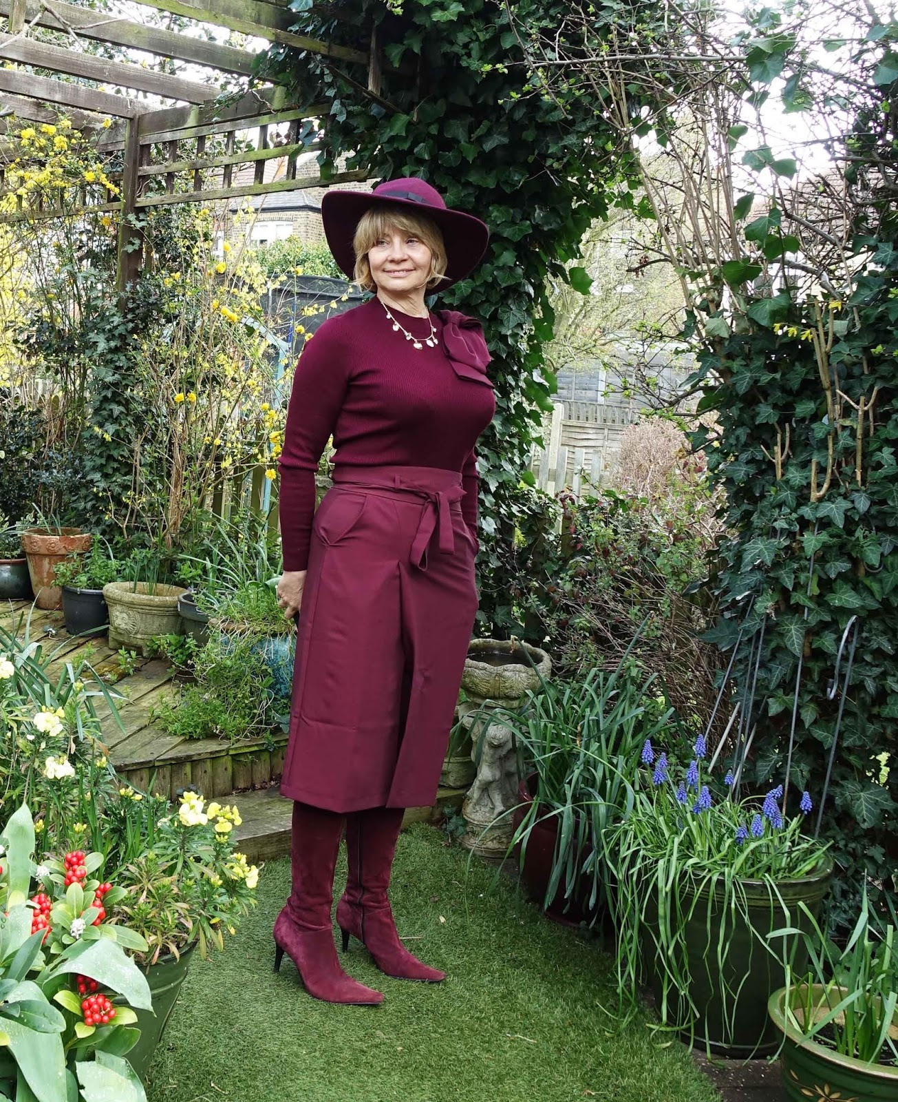 A monochrome outfit is one in a single colour, worn head to toe. In this example from over 50s blog Is This Mutton? the outfit is burgundy separates with boots and a hat.
