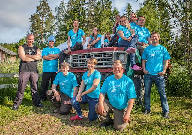 Tiimi-T-paitoihin pukeutuneita henkilöitä autonromun päällä poseeraamassa