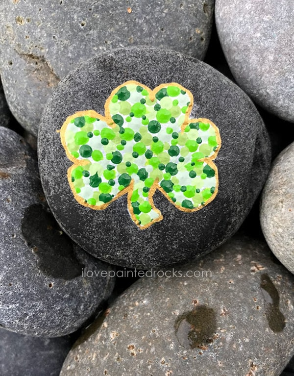 St Patrick's Day craft idea - shamrock silhouette painted rock with dot art. Learn how to make dot art with this fun and easy St Patrick's Day craft for kids or adults. #ilovepaintedrocks #stpatricksday #stpatricksdaycraft #rockpainting #paintedrocks #paintedstones #stonepainting #shamrock