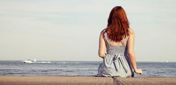 Mujer reflexionando a la orilla del mar sobre la infidelidad y el matrimonio