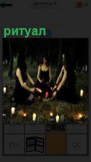 В лесу среди свечей сидят в круге девушки и совершают ритуал в вечернее время