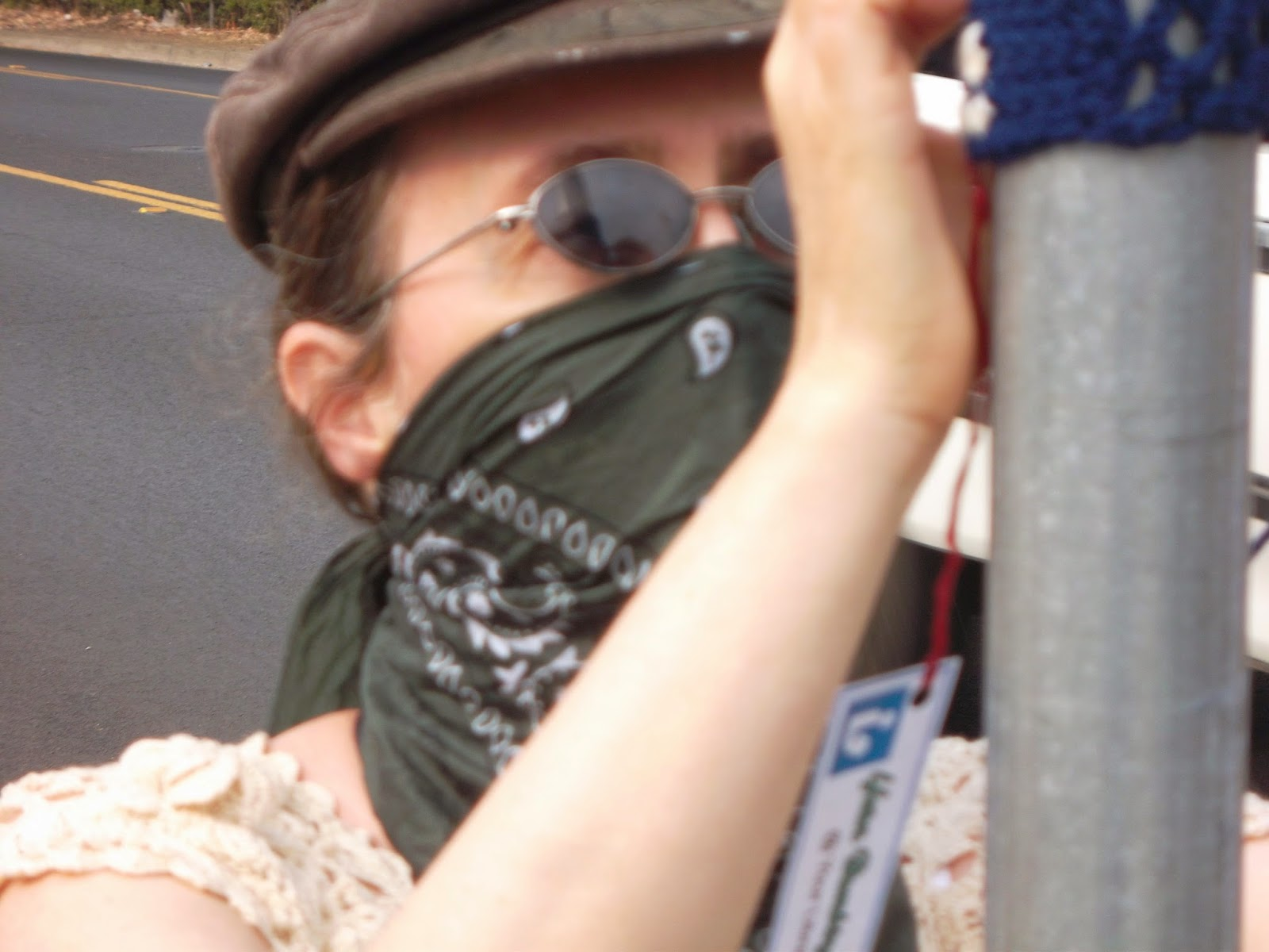 Cynthia M. Parkhill with a bandana tied over nose and mouth, attaches yarnbombing tag to bus sign pole.