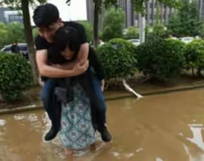 Chinese woman pictured carrying her boyfriend on her back while crossing a flooded street so 'he won't ruin his expensive leather shoes'
