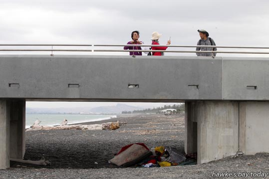 ourists take photos of Hawke's Bay scenery from the Viewing Platform on Marine Parade, Napier, just above a pile of sleeping gear, clothing, shoes and lots of condoms which belong to a homeless person. photograph