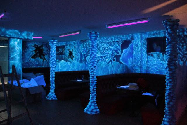 Malowanie ścian w klubie farbami fluorescencyjnymi, malowidło świecące w ciemności, black light