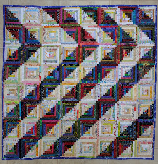 Scrap log cabin quilt with half-inch logs alternating darks and lights