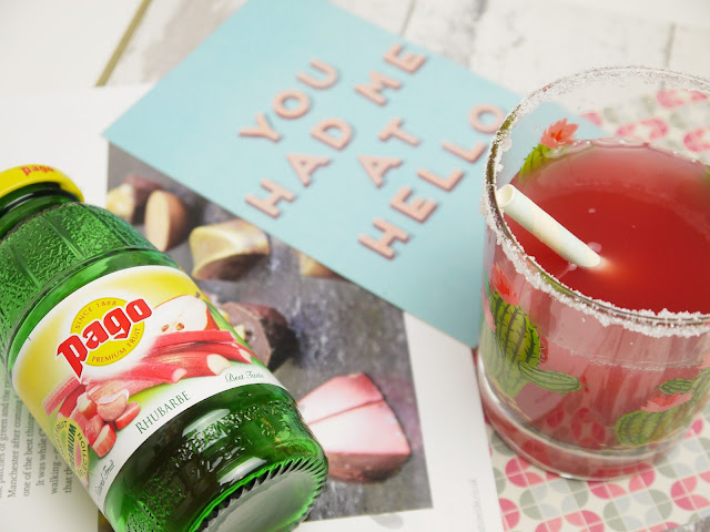 a small green glass pago juice bottle next to pink juice in a cactus print glass with a sugar dipped rim