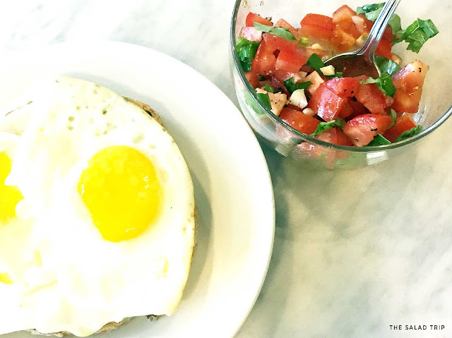 White plate with Eggs on top of bread next to a clear bowl with bruschetta mix