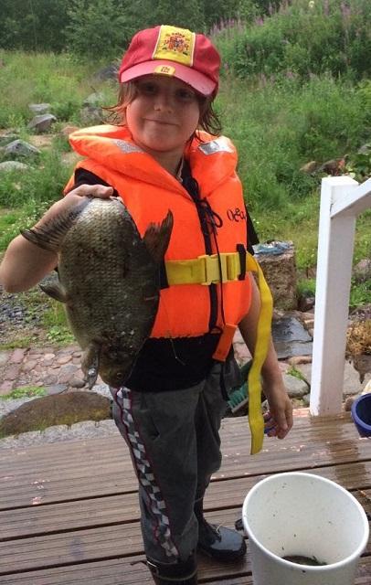 nuori kalastaja saaliin kanssa