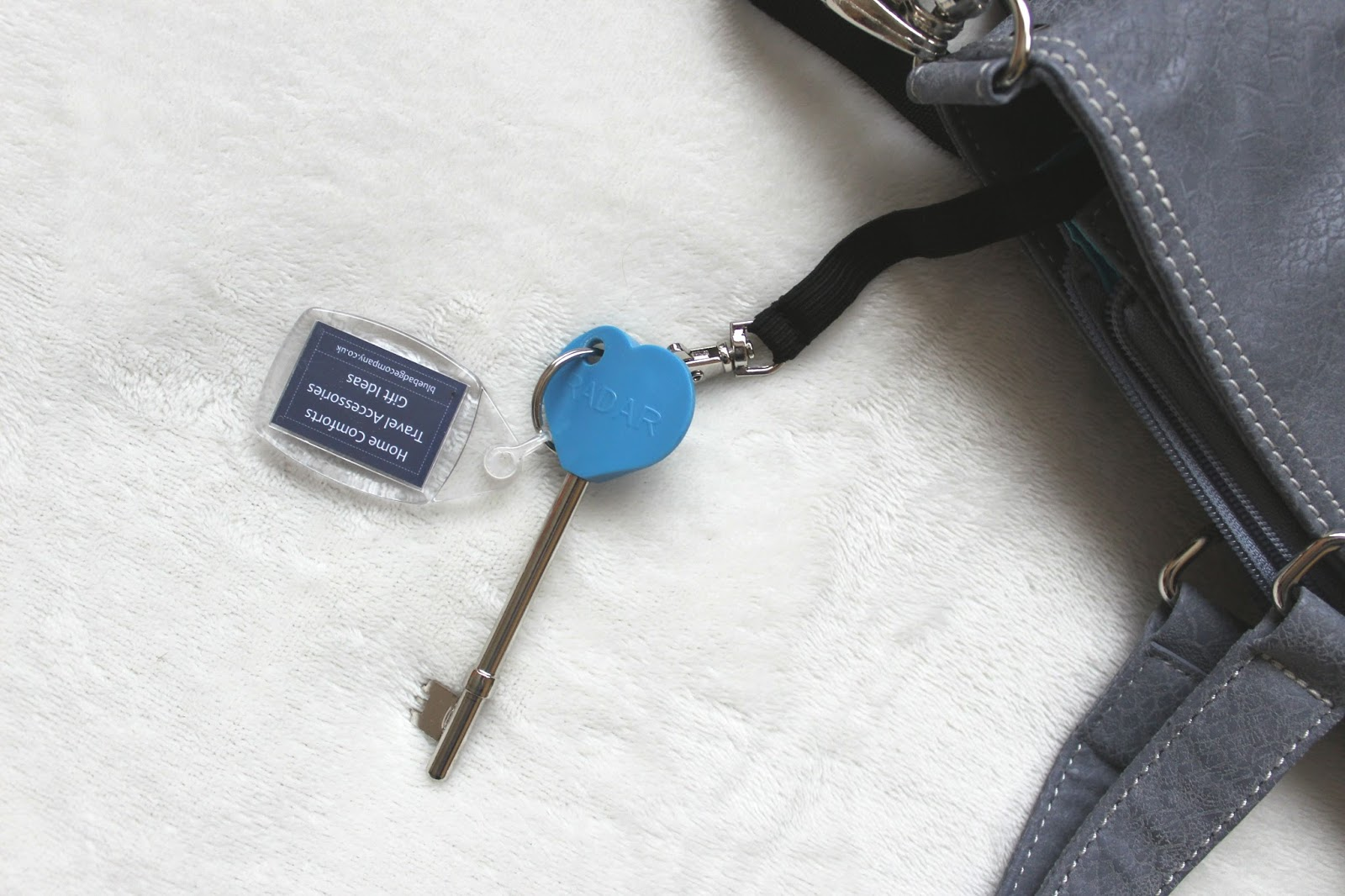 A blue key and keyring are attached to a keys clip which is hanging out of a large grey handbag.