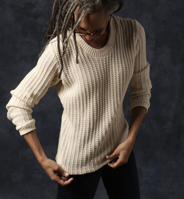 Woman looking at hem of sweater