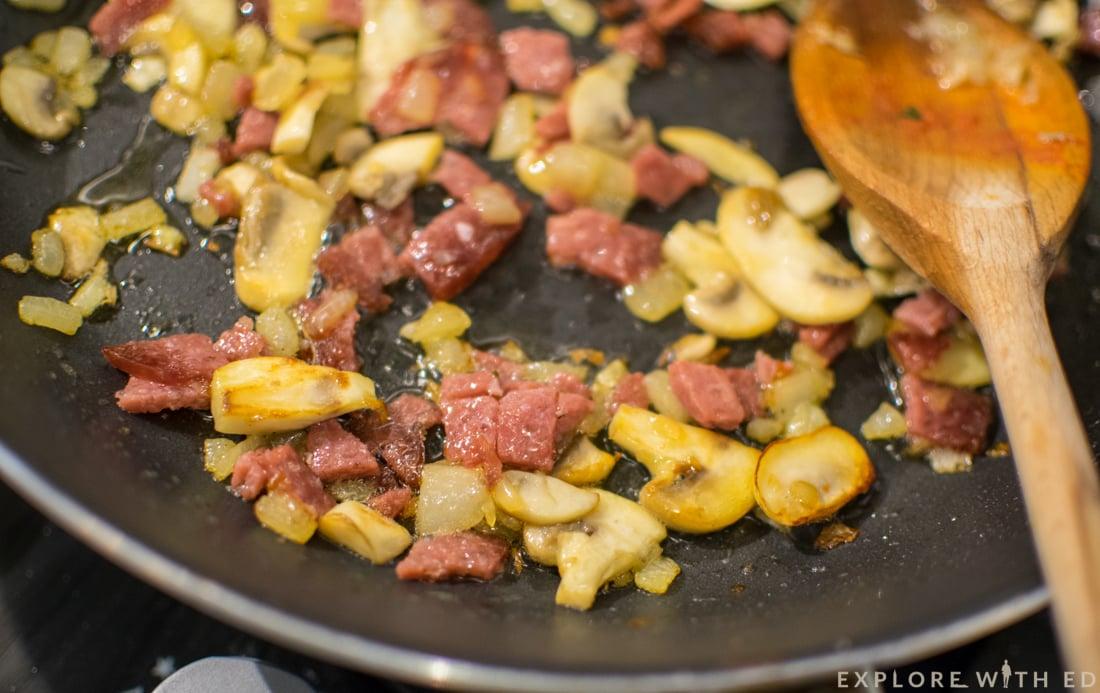 Frying onion, garlic, salami and mushroom