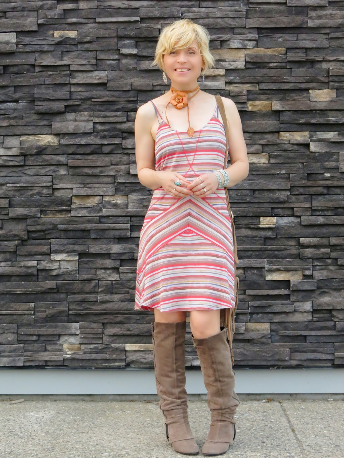 styling a striped slip dress with suede knee boots and a fringy cross-body bag