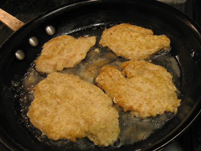 four chicken filets cooking in a pan