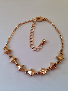a gold chain bracelet with stud details