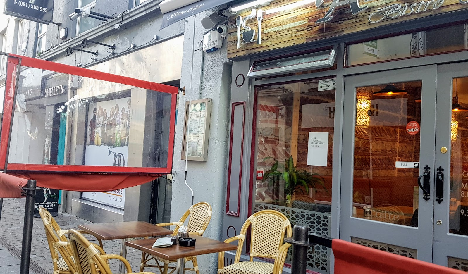 Middle-eastern cafe bistro in galway city - outdoor tables with ashtrays, wicker-work chairs, orange canvas partitions with see-through window canvas.