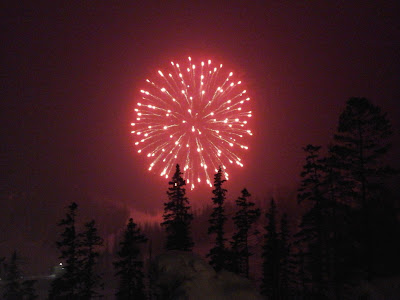 Evening winter scene with a huge red firework shinning in the night at ski area.