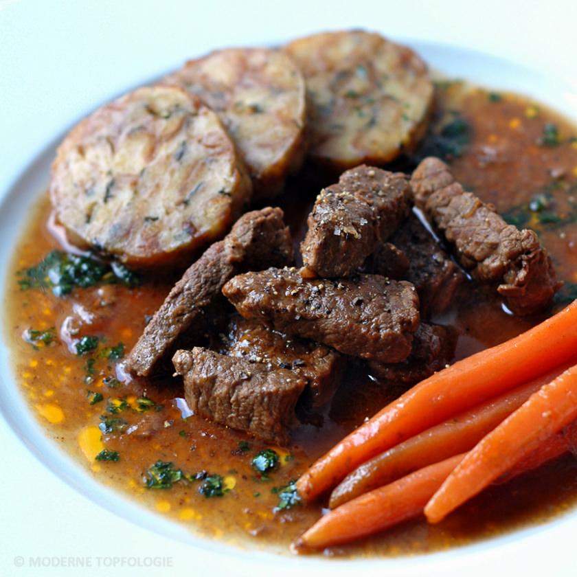 Im Guinness-Sud geschmortes Bierfleisch mit Serviettenknödel und glasierten Mini-Möhren.
