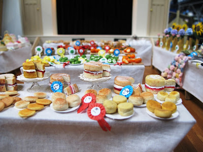 Baking with prize ribbons on a stall in a one-twelfth scale scene of a CWI wartime fundraising fete in a hall.
