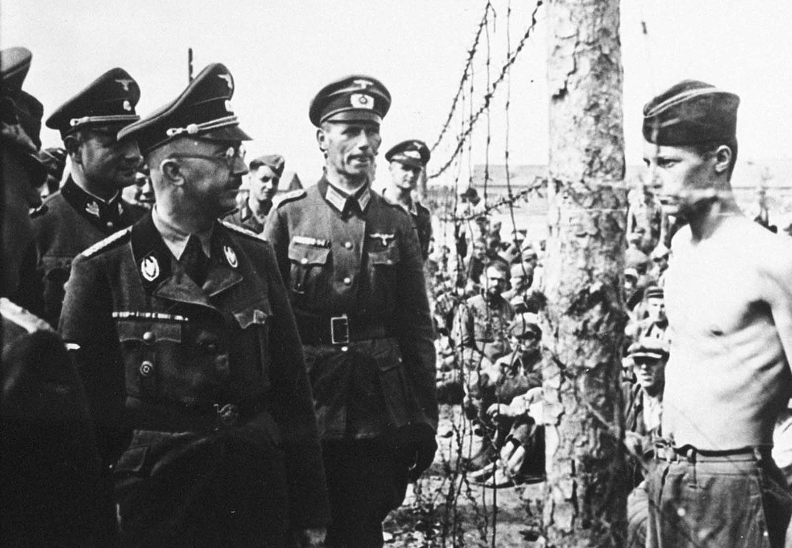 Heinrich Himmler (left, in glasses), head of the Gestapo and the Waffen-SS, inspects a prisoner-of-war camp in this from 1940-41 in Russia.