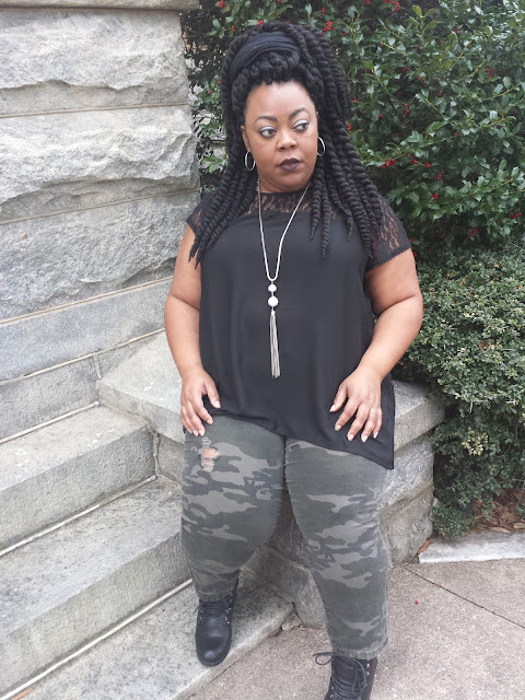 Plus size blogger sitting on steps, staring into the distance, self-reflection.