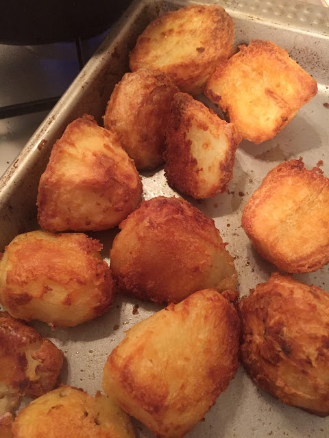 A baking tray filled with golden brown roast potatoes