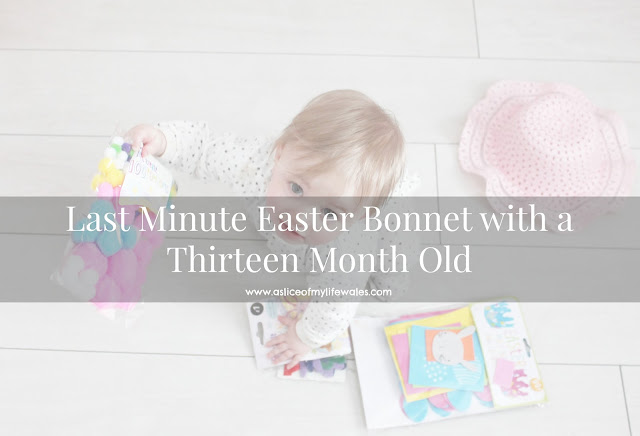 last minute easter bonnet with a thirteen month old - baby on white wooden floor looking up at camera holding craft items ready to make a bonnet