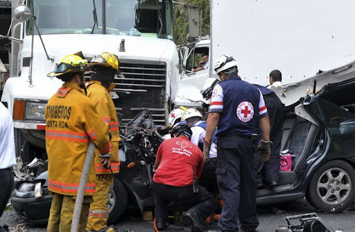 Rescue workers work at the scene of a car accident involving Costa Rica player Dennis Marshall
