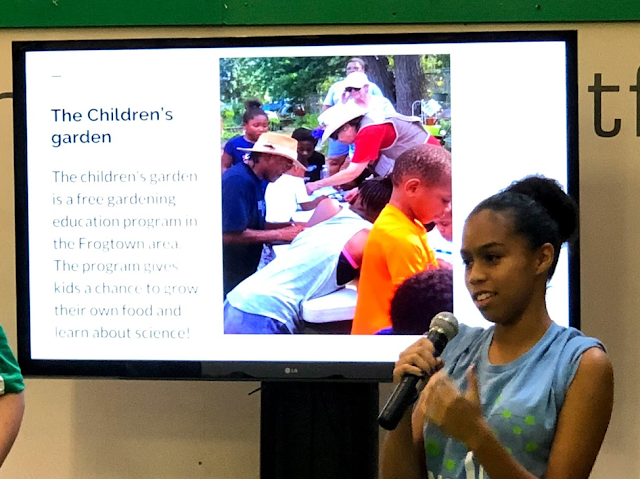 Kahlea, one of the F/R Youth Leaders, giving a presentation about their work at the Minnesota State Fair. Standing in front of a television.