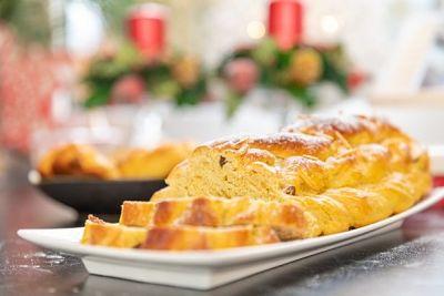 Pan dulce trenzado para navidad, con dos porciones cortadas sobre una bandeja y adornos navideños de fondo.