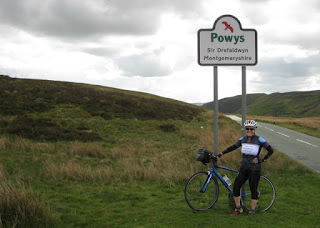 pep at the summit with Powys sign,view toward the southeast, Wales.