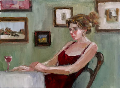 Woman seated at table with wineglass her arms on table many paintings on wall behind