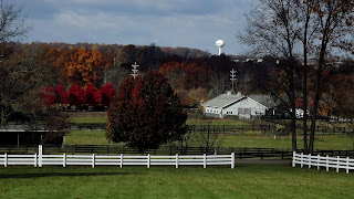 Horse farm with white fence before grey barn at the edge of a forest of Fall colors with a white water tower in the background